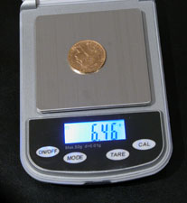 Electronic scales help identify used and worn coins. The photo demonstrates a French 20Franc Napoleon Marianne Coq which is perfect according to its weight.